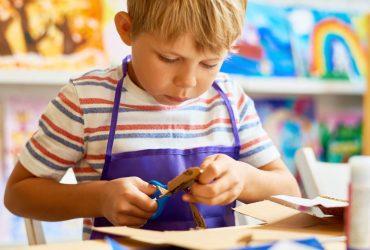 Little Boy Cutting Paper in Craft Class